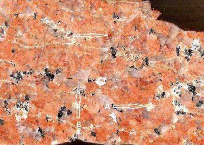 2. Detail van 2. Pijl A toont de witte plagioklaas, pijl B een kwartsklonter en pijl C roodbruine plagioklaas