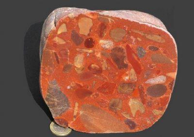 3. Kiezelconglomeraat. Als. De rode kleur wordt veroorzaakt door rijkelijke aanwezigheid van hematiet, die ook in verschillende rolstenen is doorgedrongen.