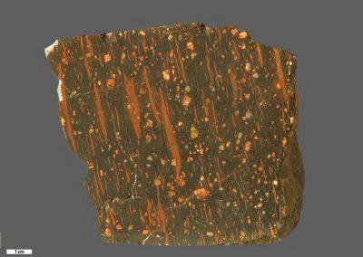 3. Ignimbriet v Dalarna. Zwarte Rännas. Fk . Een steen met een dichte, donkerbruine, bijna zwarte grondmassa.