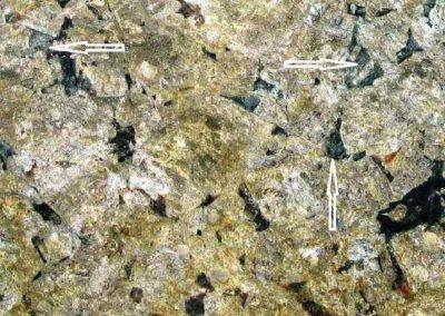 6. Detail van 5. De pijlen tonen groenachtige oeraliet. Rechtsonder zien we enkele bruinrode roestvlekjes