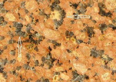 2. Detail van 1. - De pijlen tonen enkele voor Pyterliet kenmerkende kransen rond een kaliveldspaat.