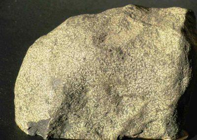 2. Nefelienbasalt. Nij Beets. Een type met een groot aantal dicht opeenliggende nefelienvlekjes. Het hier niet afgebeelde zaagvlak is nogal dicht en donker van kleur.