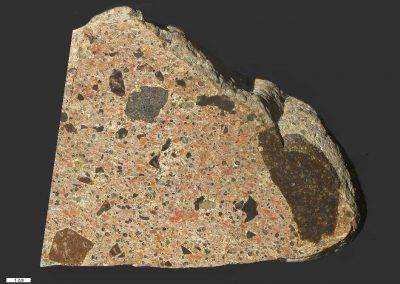 1. Breccie. Vulkanisch. Ertebolle. Dk. De grondmassa met de vele kleine steentjes is eigenlijk tuffiet.