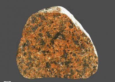 7. Vaggeryd syeniet. Als. Rond de donkere mineralen bevinden zich op verschillende plaatsen reactieranden. Dit wijst op metamorfose.