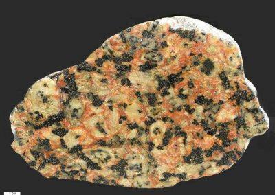 1. Monzogabbro type Nordingrå. Fynshav. Als. Dk Tijdens de stolling is omringend granitisch magma het gesteente binnengedrongen. Vandaar de rode gedeelten vn kaliveldspaat.