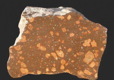 8. Rhombenporfier. Noordoostpolder. Een steen met kleine witte holte opvullingen