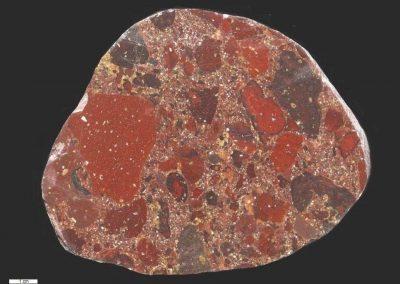 8. Vulkanische breccie. Kås Hoved, Een, waarschijnlijk door ijzer, fel rood getint type. De grondmassa is tuffietisch.